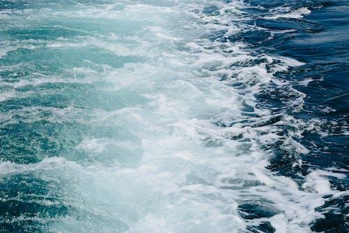 Waves behind cruise ship sailing on sea