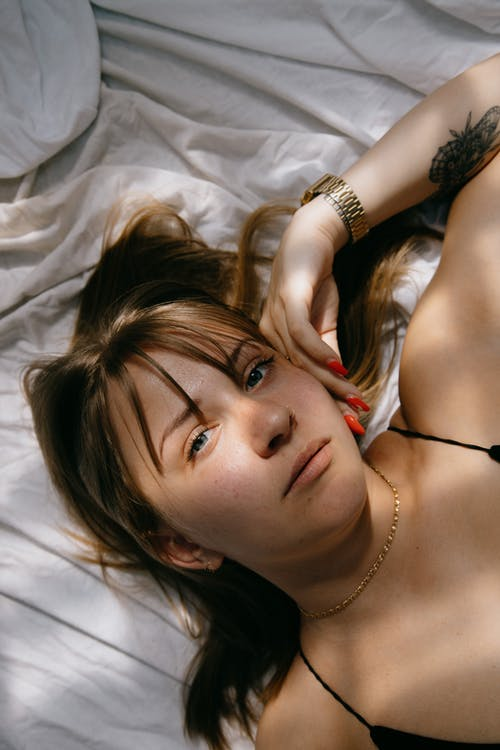 Thoughtful young woman lying on bed