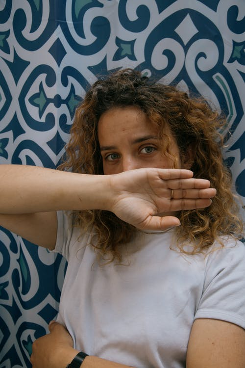 Young  female with curly hair wearing casual outfit hiding face with hand while standing against wall with colorful ornament
