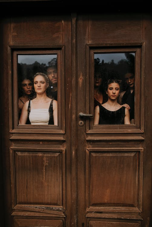 Group of people standing behind wooden entrance of building and looking out window with unhappy faces