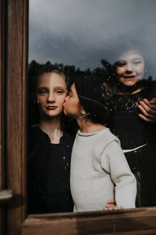 Little girl kissing elder sister while standing behind window glass with raindrops on sunny day