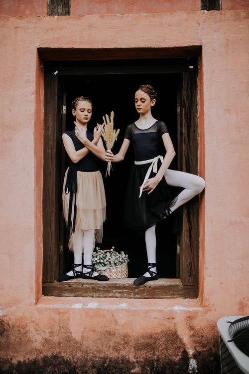 Young girls standing on windowsill