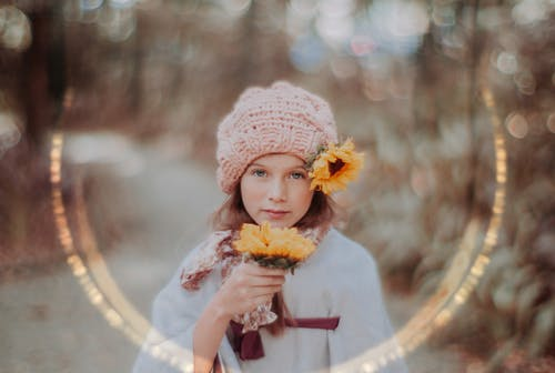 Girl in White Knit Cap Holding Yellow Flower