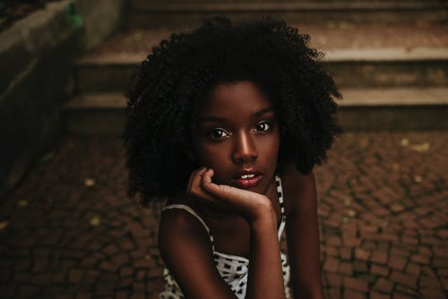 Young African American female with curly hair wearing summer dress sitting on pavement on city street and looking at camera