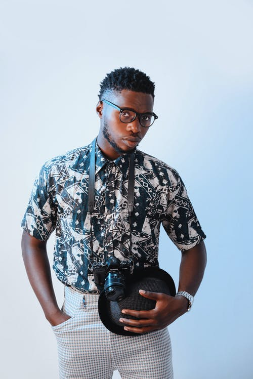 Young serious African American man with hat and photo camera wearing trendy outfit and eyeglasses standing in studio with blue wall