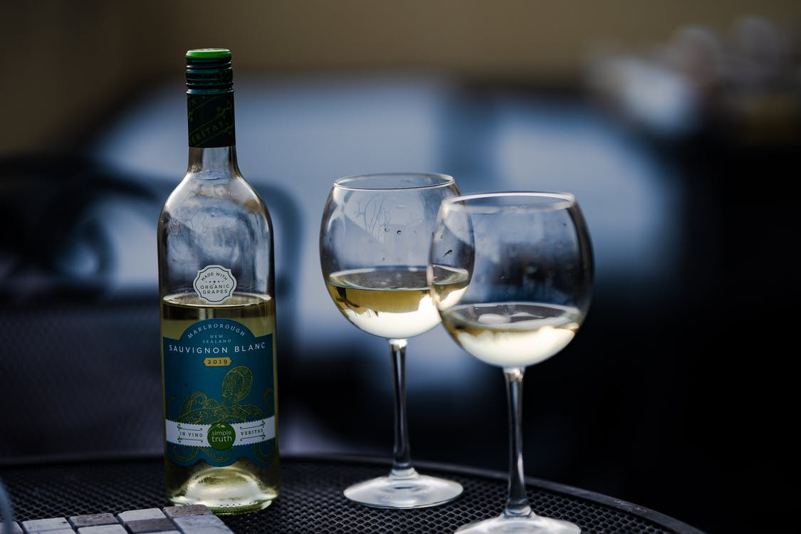 Glass bottle of wine placed near crystal wineglasses on round table in cafe