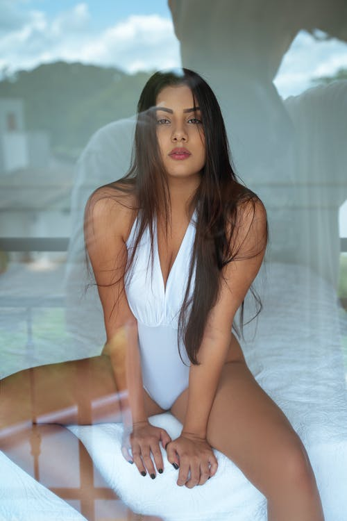 Young woman in white bodysuit sitting on bed