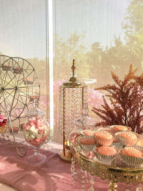 Beautifully decorated pink banquet table with various sweets for guests placed with plant branches