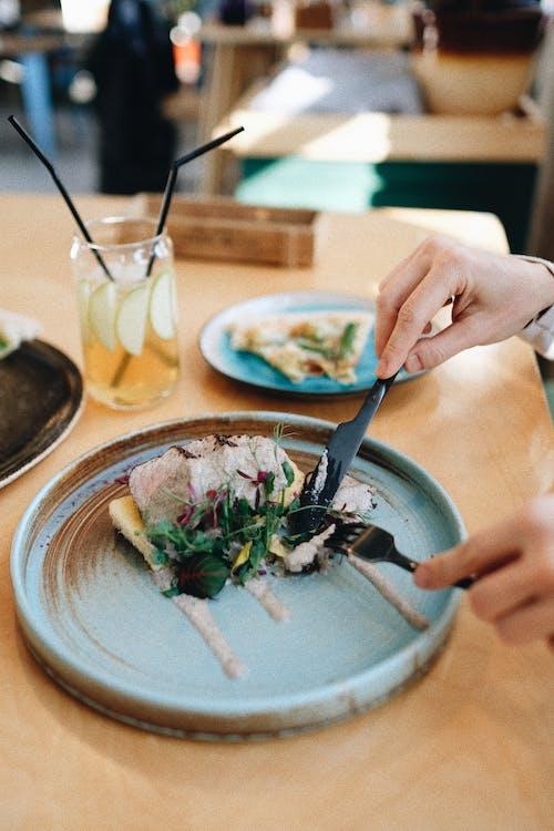 Crop person eating molecular dish in modern restaurant