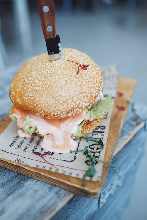 Tasty hamburger with sesame seeds on bun placed on wooden board