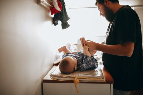 Young father changing diaper of newborn baby