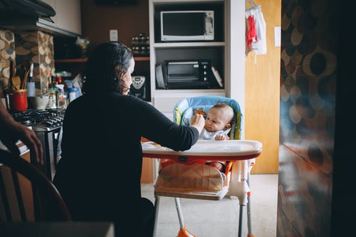 Small kid sitting in modern feeding chair eating food with nanny in cozy kitchen