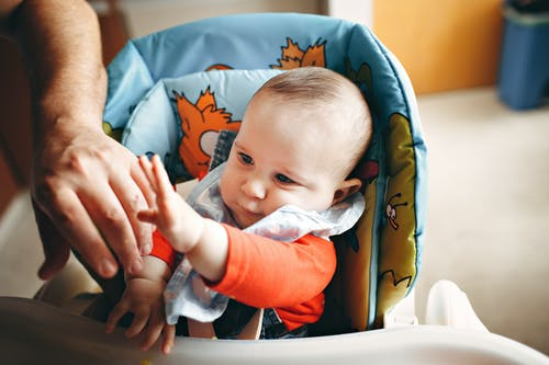 Crop person touching curious cute baby sitting in chair for feeding in kitchen