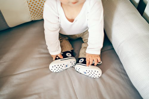 Little baby in cool shoes on bed