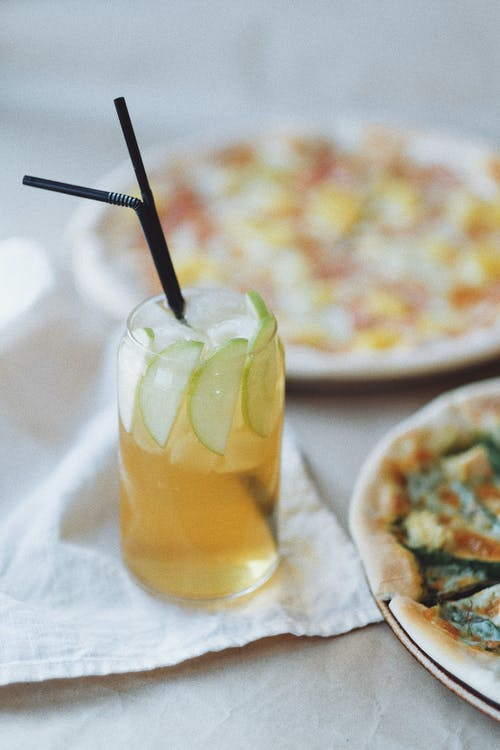 Cold fresh drink in glass with straws near pizza on table