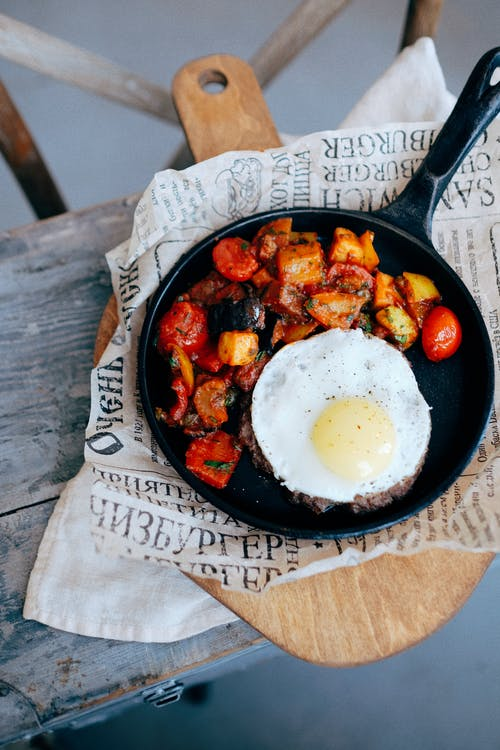 Pan with roasted vegetables and steak with egg placed on wooden board