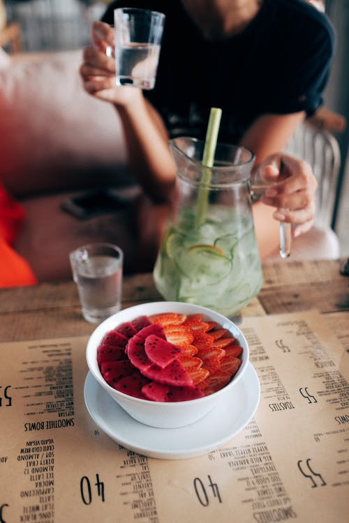 From above of healthy smoothie bowl decorated with fresh strawberries and dragon fruit and placed on table with anonymous woman drinking homemade lemonade on background