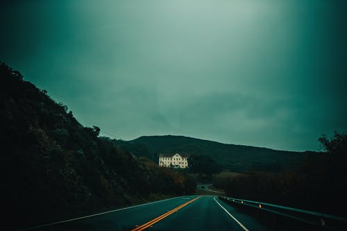 Empty highway through hilly green terrain with big white mansion