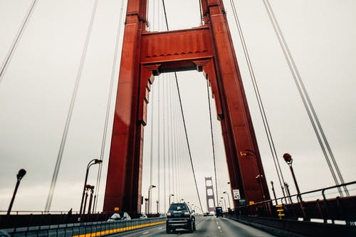 Cars riding along asphalt surface of famous Golden Gate Bridge in San Francisco on cloudy overcast day