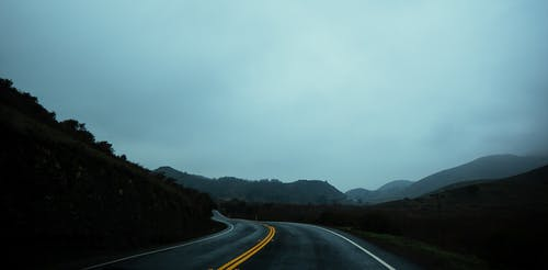 Empty highway through hilly green highlands in overcast weather