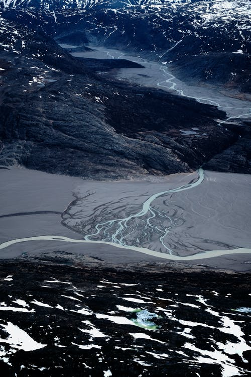 Narrow river flows in snowy mountains in winter