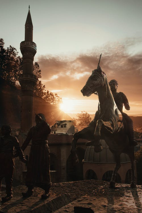 Old equestrian sculpture with men under sky at bright sundown