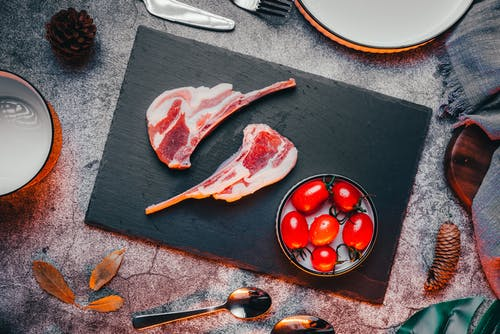 Raw Meat on Black Round Plate Beside Red Tomatoes on Black Wooden Table