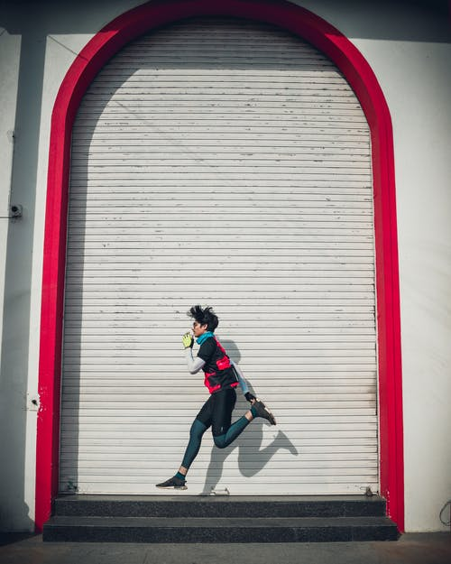 Unrecognizable stylish slim ethnic sportsman jogging near ribbed wall