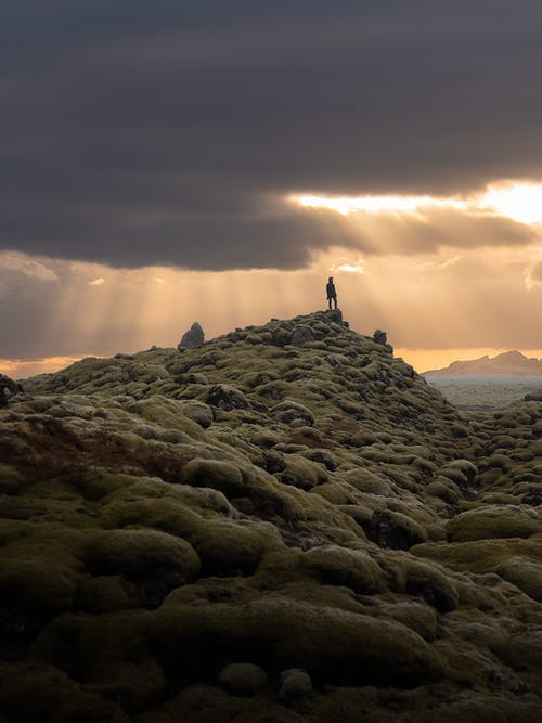 Person Standing on Rocky Hill during Sunset