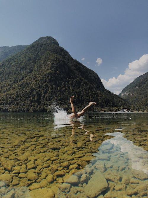 Woman in White Bikini on Water Near Green Mountain