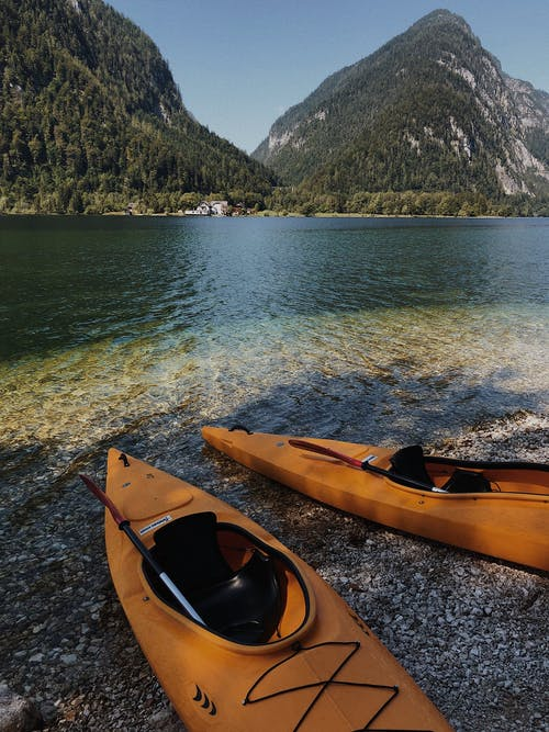 Yellow Kayak on Gray Sand Near Body of Water