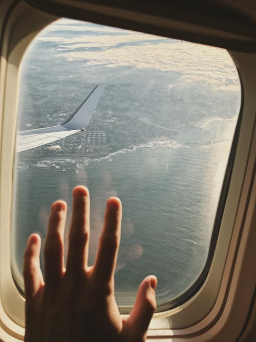 Persons Left Hand on Airplane Window