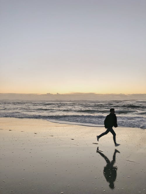 Man in Black Shirt and Pants Walking on Beach during Sunset