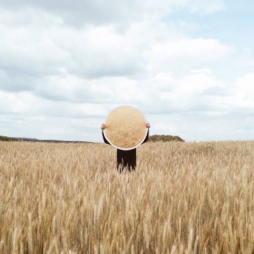 Person in Brown Hat Standing on Brown Grass Field Under White Clouds