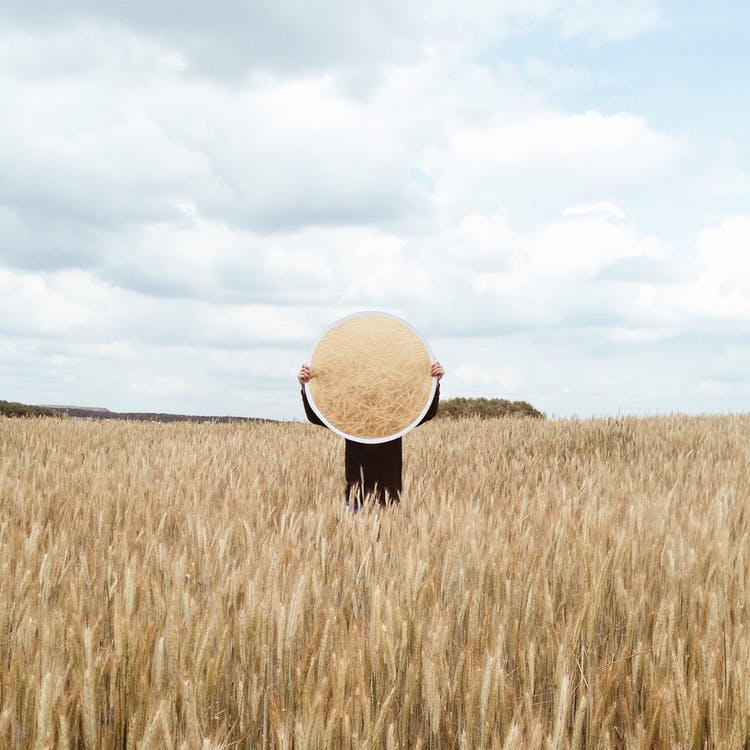 Person Holding a Mirror on an Open Field