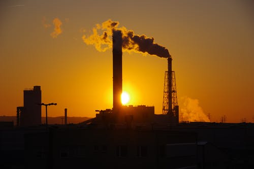 Industrial chimney with thick smoke under sky with glowing sun at dusk at power plant