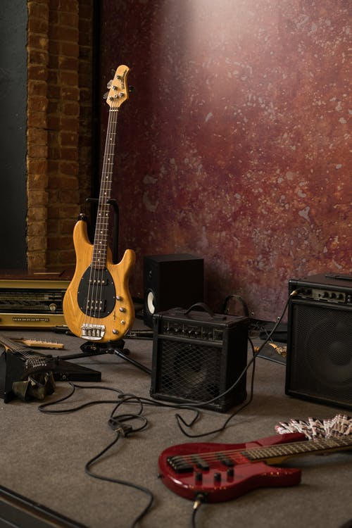 Stage in rehearsal studio with modern electric guitars and stereo acoustic system against red wall