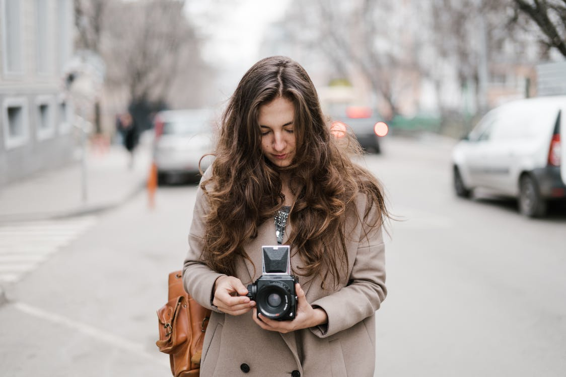 Young woman using photo camera during walk in city