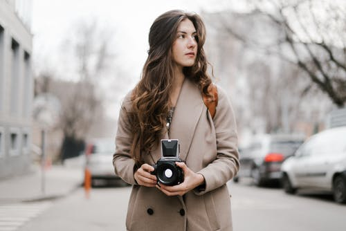 Dreamy young woman with vintage analog camera on street