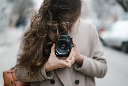 Anonymous young woman photographing with retro film camera