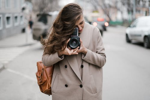 Stylish young lady in warm coat and backpack taking photos with old fashioned camera during sightseeing in downtown
