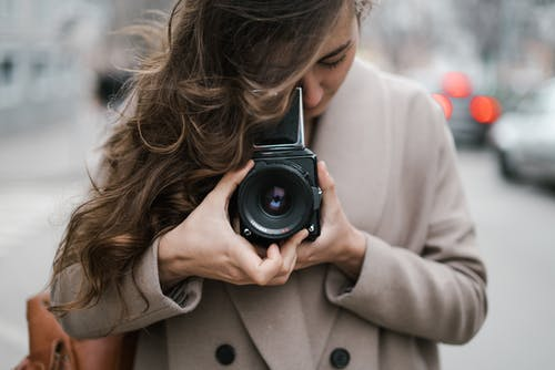 Young woman taking photos with old fashioned camera on street
