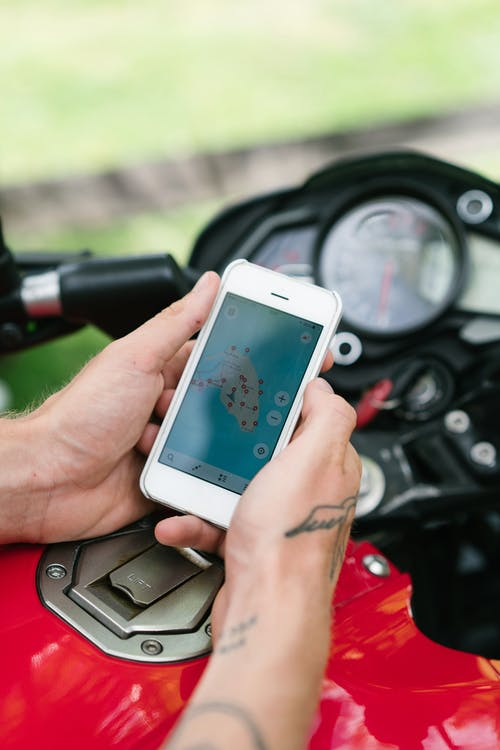 Crop man studying map on smartphone