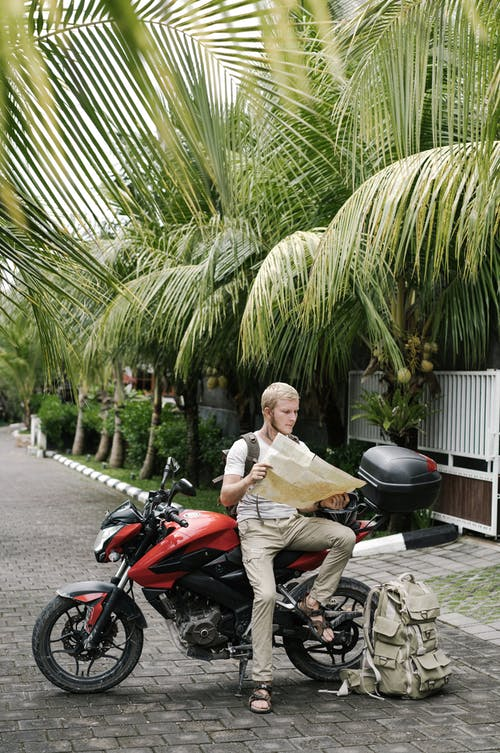 Focused man studying map leaning on motorbike