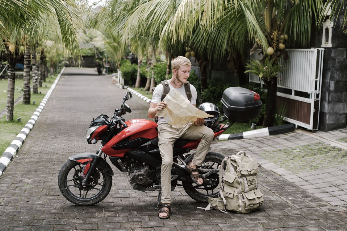 Full body male tourist in casual clothes with backpack helmet and duffle bag studying city map while leaning on parked motorbike on street under palms