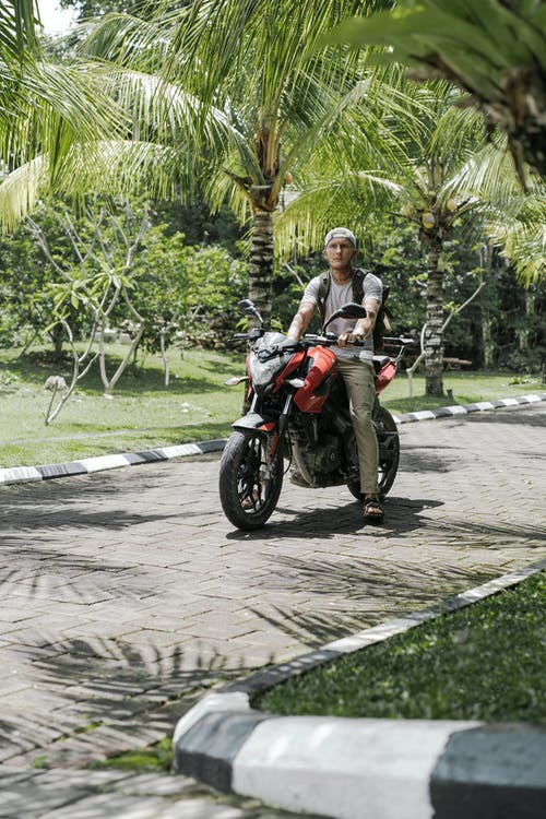 Modern biker sitting on motorcycle on pathway in tropical city