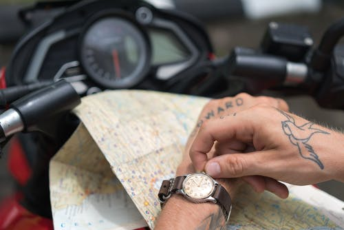 Crop tattooed man setting up watch against map and motorbike
