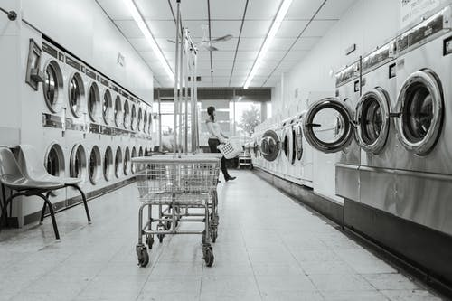 Grayscale Photography of Woman in Laundry Shop
