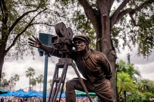 Man in Brown Long Sleeve Shirt Holding Camera Statue