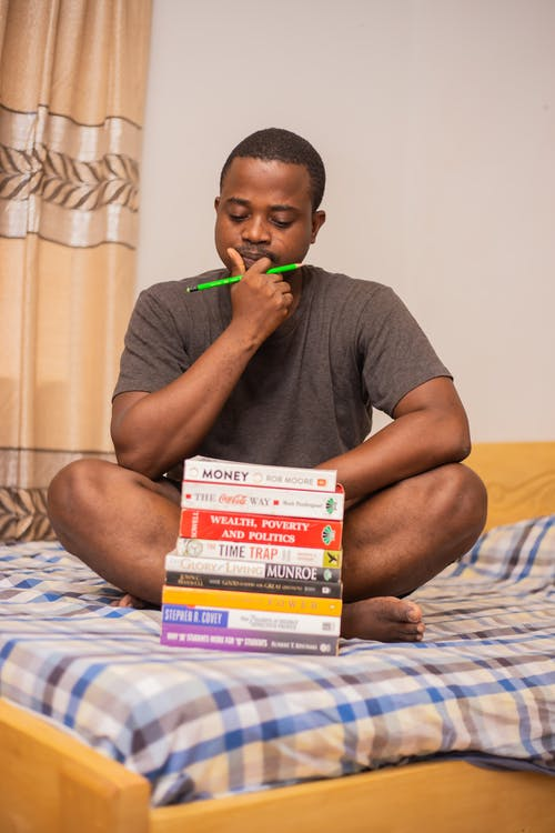Pensive young black guy doing homework in bedroom